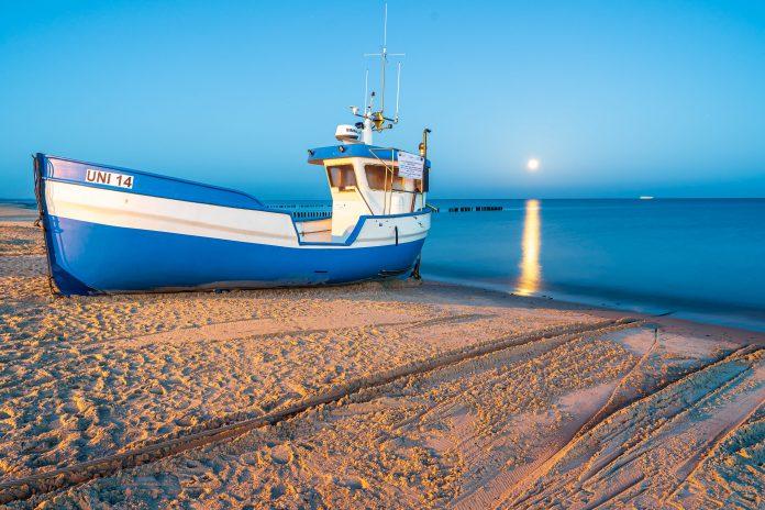 Mielno noclegi: łódka rybacka i widok na morze w tle